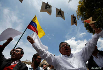 "Supporters of the peace deal signed between the government and Revolutionary Armed Forces of Colombia rebels display a Colombian flag during a rally in front the Narino Palace, in Bogota, Colombia, Oct. 5, 2016. The placards read ""Peace."""
