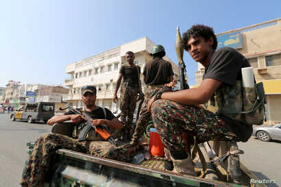 FILE - Houthi militants patrol a street where pro-Houthi protesters demonstrated against the Saudi-led coalition in Hodeidah, Yemen.