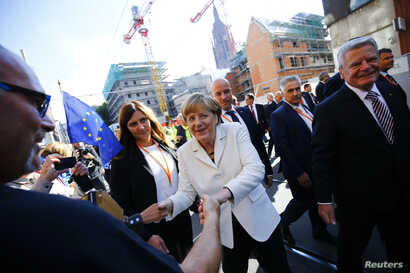 German President Joachim Gauck (R) and Chancellor Angela Merkel (C) meet wellwishers in the streets of Frankfurt, Germany, October 3, 2015. Germany's political leaders celebrate the country's 25th anniversary since the reunification of East and West ...