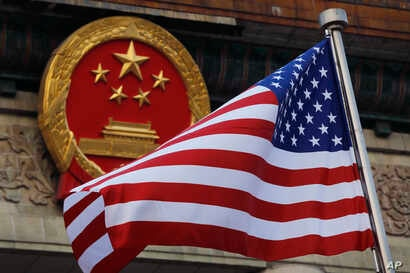 FILE - In this Nov. 9, 2017, file photo, an American flag is flown next to the Chinese national emblem during a welcome ceremony for visiting U.S. China says accusations against an alleged spy of attempting to steal trade secrets from several America