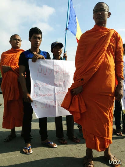 People hold signs that protest a deal signed on Friday that would send refugees from Australian detention centers to Cambodia, near the Australian embassy, in Phnom Penh, Cambodia, Sept. 26, 2014. (Robert Carmichael/VOA