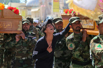 Mourners chant slogans against the Islamic State group during the funeral procession of three members of a Shi'ite group, Asa'ib Ahl al-Haq, or League of the Righteous, who were killed in Tikrit while fighting Islamic militants, in Najaf, 100 miles (...