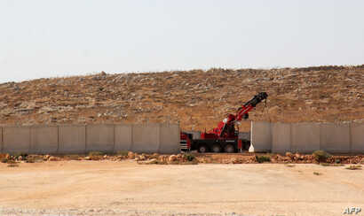 A picture taken in the Syrian village of Kafr Lusein, north of the Bab al-Hawa border crossing, Oct. 7, 2017, shows a crane parked next to a 3-meter-high fortification, built by the Turkish government along its border with Syria. The Britain-based Sy...