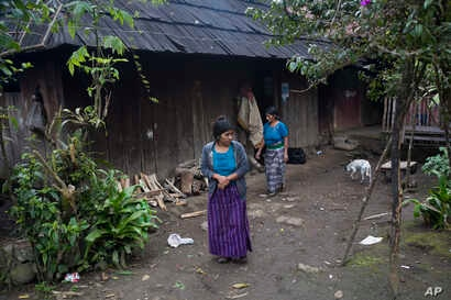 Catarina Alonzo Perez, mother of Felipe Gomez Alonzo, and her sister-in-law Maria, step outside their home in Yalambojoch, Guatemala, Dec. 29, 2018.