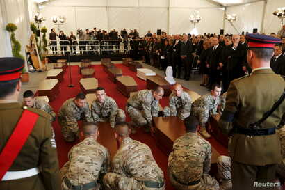 Armed Forces of Malta soldiers lay down coffins with the bodies of migrants at an inter-faith burial service at Mater Dei Hospital in Tal-Qroqq, outside Valletta, April 23, 2015. European Union leaders who decided last year to halt the rescue of migr...