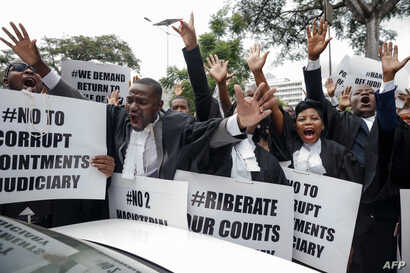 """Lawyers of the Law Society of Zimbabwe bar association take part in a """"March for Justice"""" toward the Constitutional Court in Harare on Jan. 29, 2019, to call for restoration of the rule of law, respect of human rights as well as the country's Constit..."""