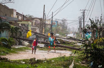 Residents walk near downed power lines felled by Hurricane Irma, in Caibarien, Cuba, Sept. 9, 2017. There were no reports of deaths or injuries.
