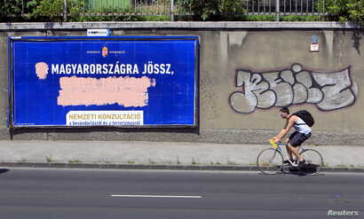 Government billboards vilifying immigrants destroyed by opposition activists are seen in Budapest, Hungary, June 10, 2015. A spoof Hungarian political party is mocking the government's anti-immigrant rhetoric.