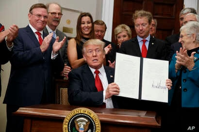 President Donald Trump shows an executive order on health care that he signed in the Roosevelt Room of the White House, Thursday, Oct. 12, 2017, in Washington.