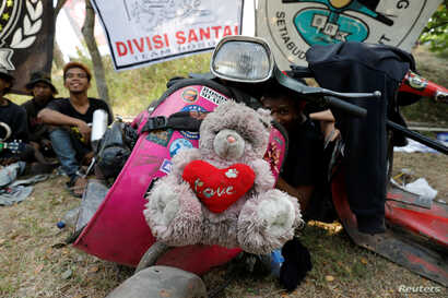 FILE - A stuffed toy mascot is tied to the front of a modified Vespa at a weekend festival for extreme Vespas in Semarang, Central Java, Indonesia, July 22, 2018.