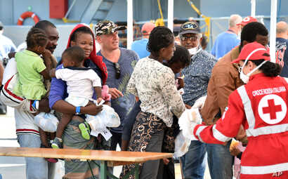 Migrants line up at a Red Cross tent after they disembarked from the Irish Navy vessel LE Niamh at the Messina harbor in Sicily, Italy, Aug. 24, 2015.