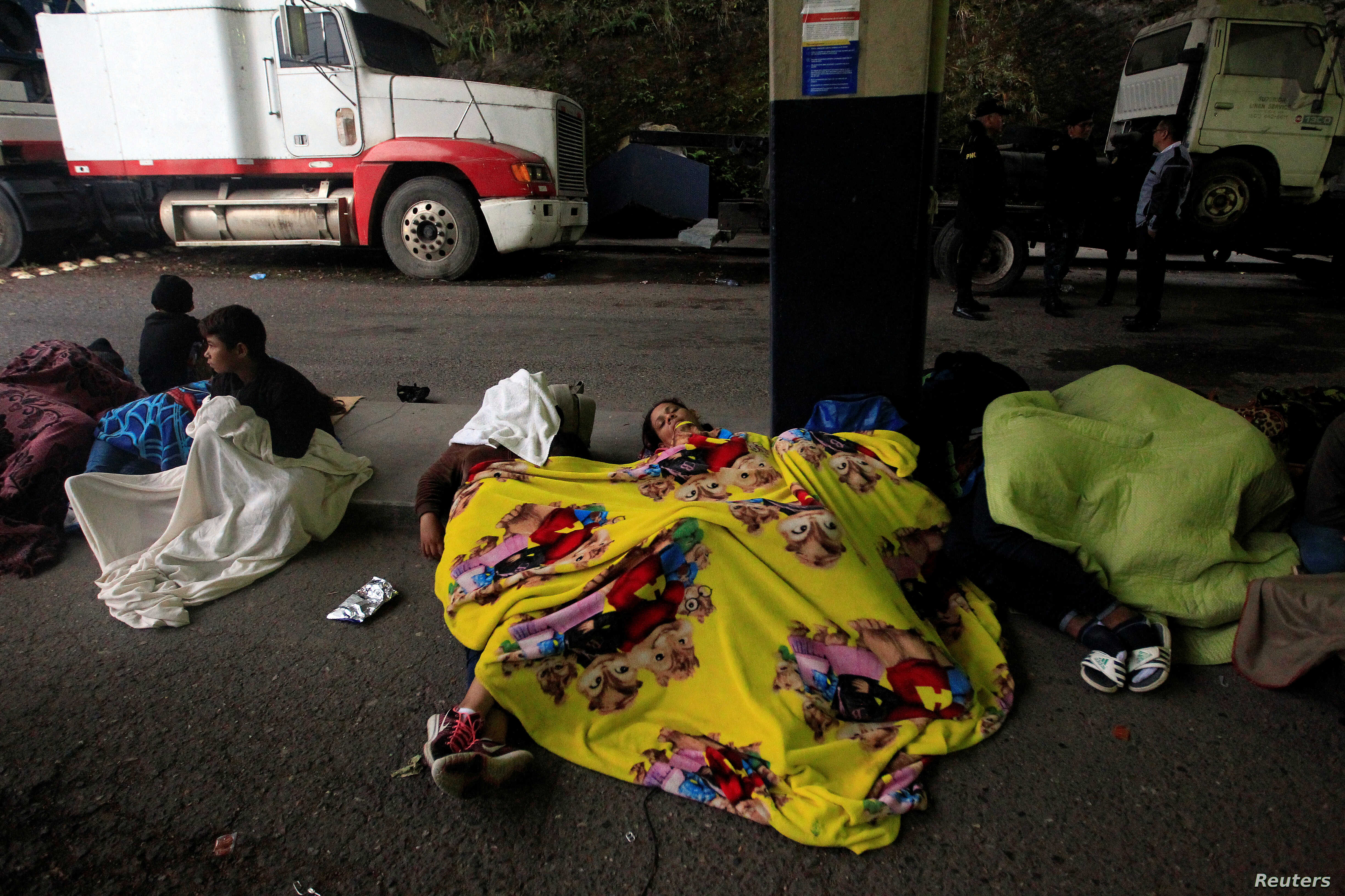 Migrants from Honduras, part of a new caravan from Central America trying to reach the United States, sleep on the ground at the Agua Caliente border checkpoint, in Esquipulas, Guatemala, Jan. 16, 2019.