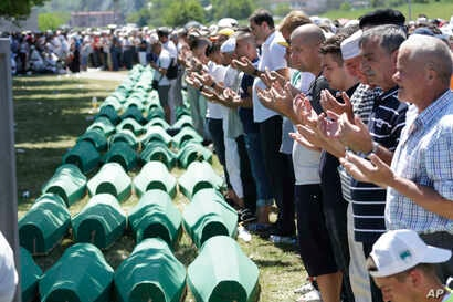 Bosnian Muslims pray in front of coffins during a reburial ceremony for dozens of newly identified victims of the 1995 massacre, at the memorial center of Potocari near Srebrenica, 150 km northeast of Sarajevo, Bosnia, July 11, 2017.