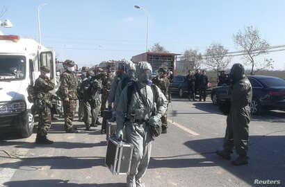 Paramilitary police officers in protective suits make their way to the site following explosion at the pesticide plant owned by Tianjiayi Chemical, in Xiangshui county, Yancheng, Jiangsu province, China, March 22, 2019.