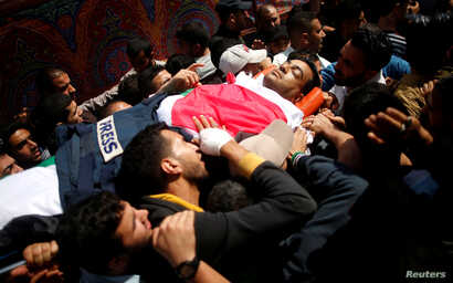 Colleagues of Palestinian journalist Yasser Murtaja, 31, who died of his wounds during clashes at the Israel-Gaza border Friday, carry his body during his funeral in Gaza city, April 7, 2018.