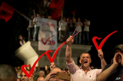 """Supporters of the opposition party """"Vetevendosje"""" hold heart signs during the closing election campaign rally in Kosovo capital Pristina, June 9, 2017. Kosovars go to the polls Sunday to choose the new 120-seat parliament."""