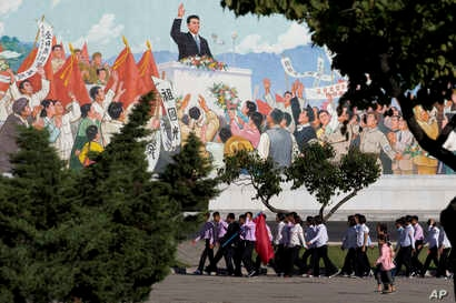 North Koreans youths march in a group past a mural as the capital prepares for the 70th anniversary of North Korea's founding day in Pyongyang, North Korea, Sept. 7, 2018.