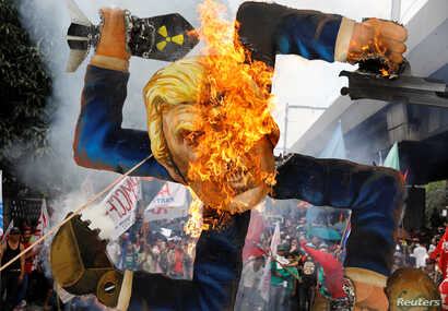 Protesters burn an effigy of U.S. President Donald Trump, who is attending the Association of Southeast Asian Nations (ASEAN) Summit and related meetings in Manila, Philippines, Nov. 13, 2017.