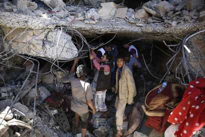 People search for survivors under the rubble of a house destroyed by Saudi-led airstrikes that killed a TV director, his wife, and three children in Sanaa, Yemen, Wednesday, Feb. 10, 2016.