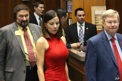 Arizona state Rep. Michelle Ugenti-Rita, center, leaves the House speaker's office along with Reps. Jay Lawrence, left, and Vince Leach, right, in Phoenix, Arizona, Feb. 1, 2018.