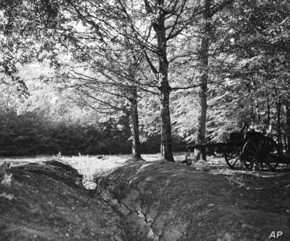 FILE - A World War I trench and artillery piece remain in the dark interior of Belleau Wood in France, June 5, 1948. The Battle of Belleau Wood, between U.S. Marines and German troops, was fought here between June 1-26, 1918.