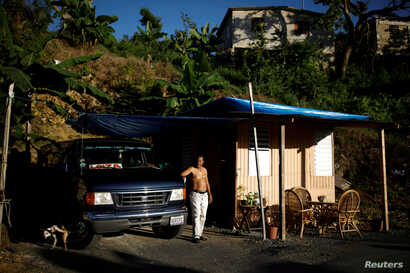 """Jorge Salgado poses for a picture next to a house he built with parts of his house, which was destroyed by Hurricane Maria, Dec. 12, 2017. Salgado said: """"I lost everything, but we have to keep living."""""""