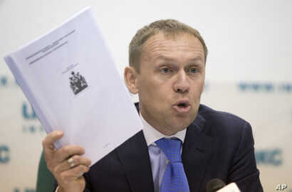 Andrei Lugovoi holds papers he which he said he got from Scotland Yard, during press conference in Moscow, Russia, March 12, 2013, about the 2006 poisoning of former Russian agent turned Kremlin critic Alexander Litvinenko in London.