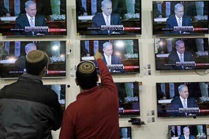Israelis watch  Prime Minister Benjamin Netanyahu address the U.S. Congress, in a shop in the city of Netivot, March 3, 2015.