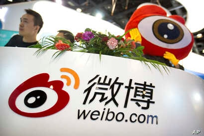 Staff members wait for visitors at a booth for Chinese microblogging website Sina Weibo at the Global Mobile Internet Conference  in Beijing, April 27, 2017. The event features current and future trends in the mobile Internet industry.