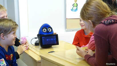 FILE - Students use a mathematics teaching robot, OVObot, during their lesson at the school in Tampere, Finland, March 27, 2017.