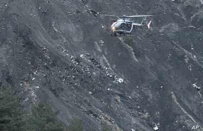 A recue helicopter flies over debris of the Germanwings passenger jet, scattered on the mountain side, near Seyne les Alpes, French Alps, March 24, 2015.