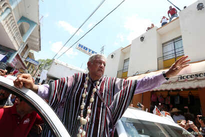 FILE - Leftist front-runner Andres Manuel Lopez Obrador of the National Regeneration Movement (MORENA) waves to supporters after a campaign rally in Tlapa de Comonfort, in Guerrero state, Mexico, June 7, 2018.