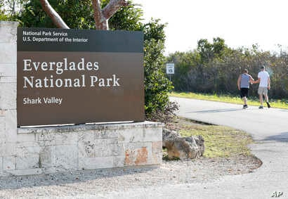 Visitors walk past a sign for Everglades National Park as they enter from overflow parking, Jan. 2, 2019, in Everglades National Park, Fla. Human feces, overflowing garbage, illegal off-roading and other damaging behavior in fragile areas were beginn...