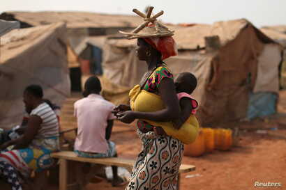 FILE - A woman carries her child in a camp sheltering internally displaced people next to the M'Poko international airport, February 13, 2016.