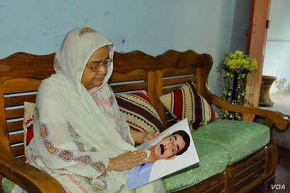 Hajera Khatun, 70, with the photo of her son Sajedul Islam Shumon, who became a victim of enforced disappearance in 2013. (A. Rajjak for VOA)