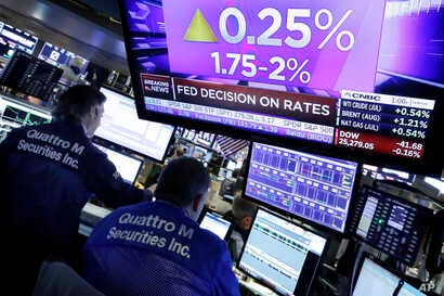 A television screen on the floor of the New York Stock Exchange shows the rate decision of the Federal Reserve, June 13, 2018.