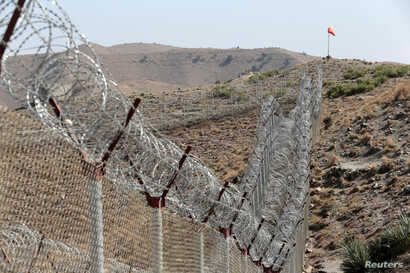 FILE - A view of the border fence outside the Kitton outpost on the border with Afghanistan in North Waziristan, Pakistan, Oct. 18, 2017.