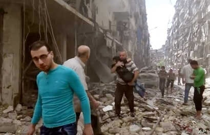 FILE - Image made from video and posted online from Validated UGC, a man carries a child after airstrikes hit Aleppo, Syria.