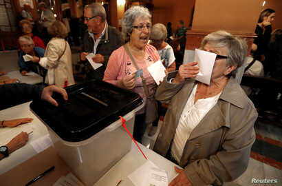 A woman kisses a ballot before voting at a polling station for the banned independence referendum in Barcelona, Spain, Oct. 1, 2017.