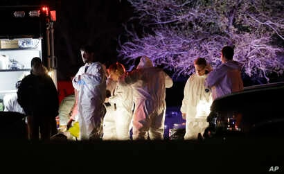 Members of law enforcement stage near the area where a suspect in a series of bombing attacks in Austin blew himself up as authorities closed in, March 21, 2018, in Round Rock, Texas.