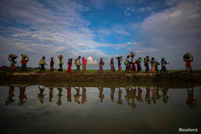FILE - Rohingya refugees are reflected in rain water along an embankment next to paddy fields after fleeing from Myanmar into Palang Khali, near Cox's Bazar, Bangladesh, Nov. 2, 2017. One year after the military crackdown that forced about 700,000 to...
