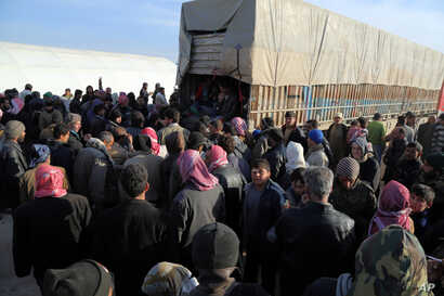In this photo provided by Turkey's Islamic aid group of IHH, Syrians fleeing the conflicts in Azaz region congregate at the Bab al-Salam border gate, Syria, Feb. 5, 2016.