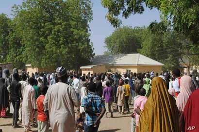 People gather outside the general hospital where the kidnapped girls from the Government Girls Science and Technical College Dapchi who were released are being treatedd, in Dapchi, Nigeria, March 21, 2018.