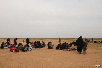 Women gather to receive humanitarian aid while they wait for transport to overcrowded Syrian camps, near Baghuz in Deir el-Zour, Syria, Feb. 26, 2019. (H.Murdock/VOA)