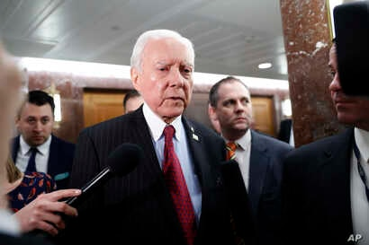 Senate Health, Education, Labor and Pensions Committee member Sen. Orrin Hatch, center, leaves the committee's executive session on Education Secretary-designate Betsy DeVos, on Capitol Hill in Washington, Jan. 31, 2017.