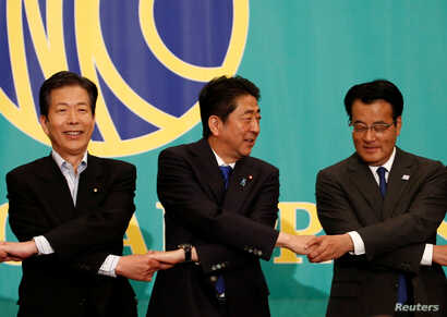 Japan's Prime Minister and leader of the ruling Liberal Democratic Party (LDP) Shinzo Abe (C), the leader of the Democratic Party Katsuya Okada (R) and Komeito party leader, Natsuo Yamaguchi, attend a debate with rival party leaders ahead of July 10 ...