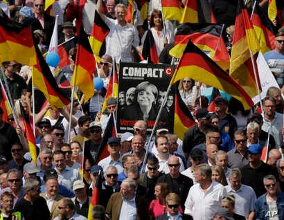 AfD supporters march with a poster showing German Chancellor Angela Merkel in Berlin, Germany, Sunday, May 27, 2018.