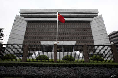 FILE - A Chinese national flag flutters in front of  the Shanghai's No. 1 People's Intermediate Court in Shanghai, China.