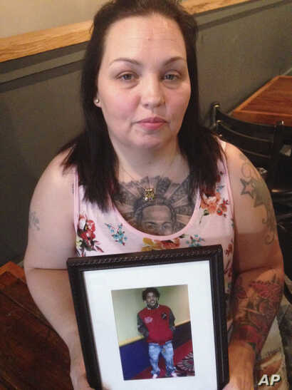 FILE - In this May 19, 2017, photo, Angela Williams holds a photo of her 18-year-old son, Cameron D. Pugh, who was killed as part of a murder spree that hit Louisville, Kentucky, in 2016.
