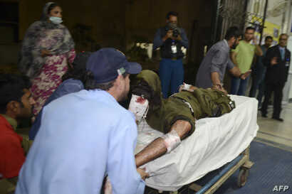 Pakistani rescue workers push a stretcher carrying an injured man to the hospital following the blast of a motorcycle bomb attack in Lahore on March 14, 2018.